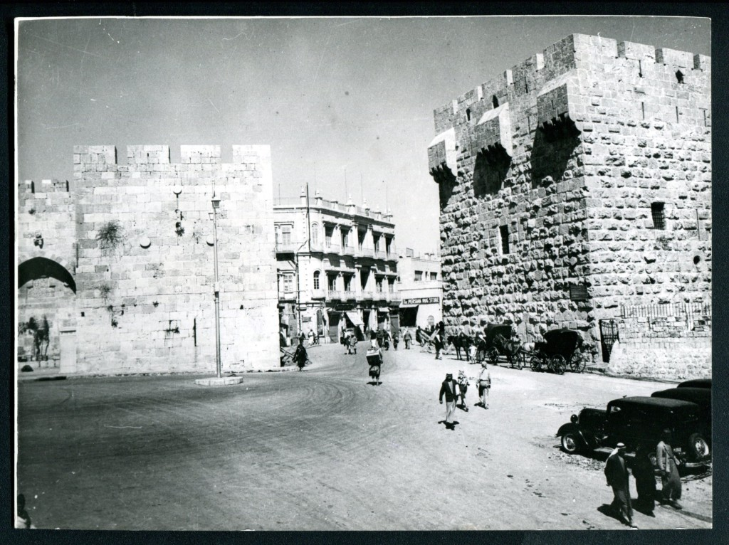 Photo of Yafa Gate, Old City, Jerusalem. Early 20th Century. People, horses and carriages, vehicles, and buildings.